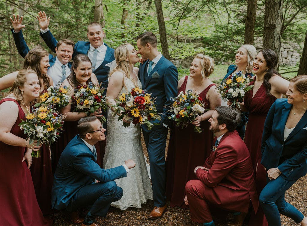 Brilliant Blue suits paired with rustic, deep red bridesmaids dresses. Groomswomen ad groomsmen in coordinating suits
