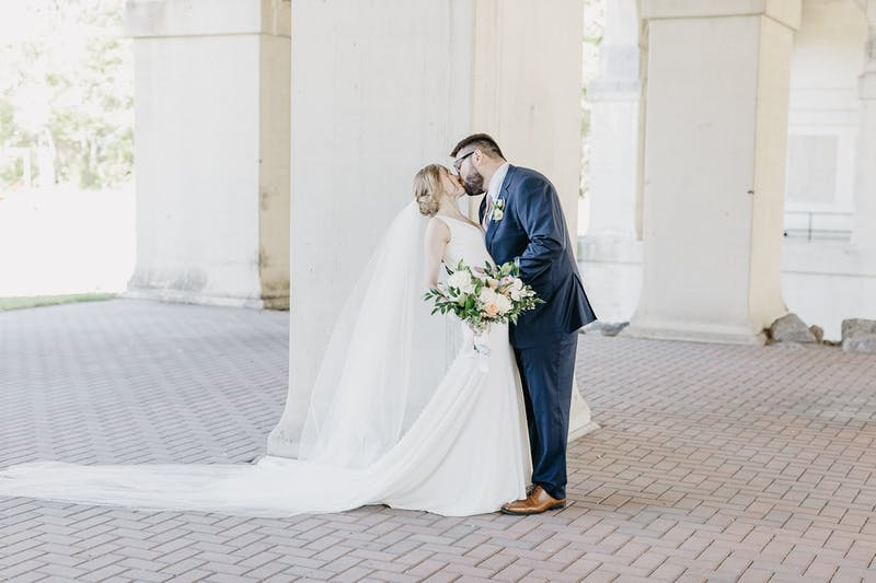 Bride and Groom Kissing in Navy Blue Suit