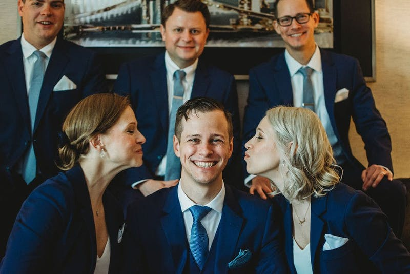 a grooms and his groomshumans in brilliant blue suits