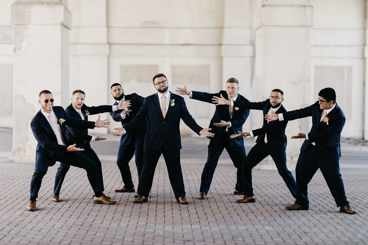 Groomsmen proud of their groom on his wedding day, wearing Navy Suits with mauve ties from Birdy Grey
