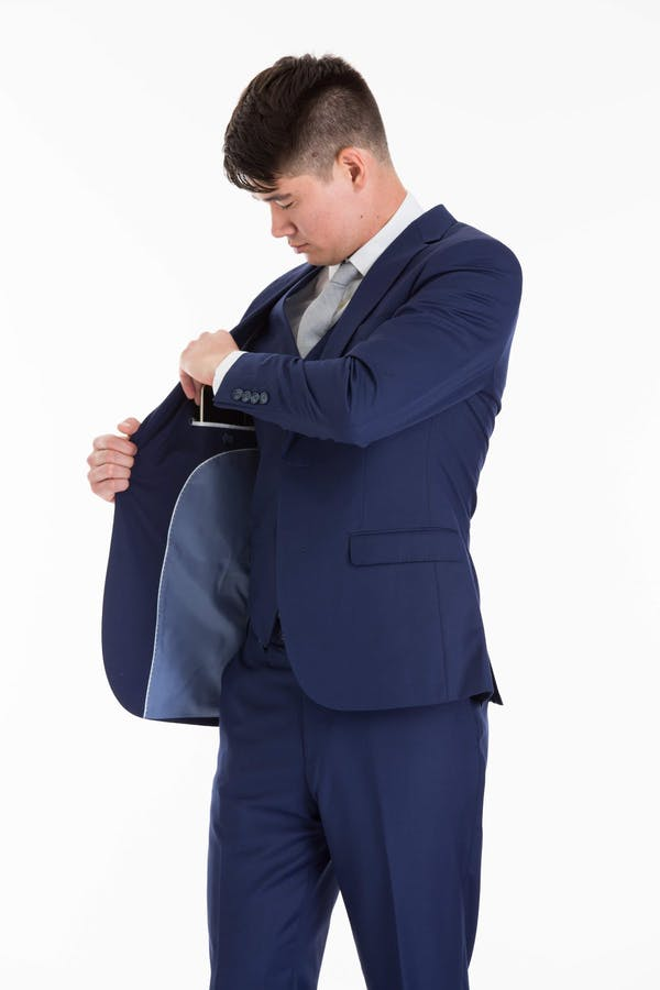 How should I carry my phone, wallet, and keys in my suit pockets?