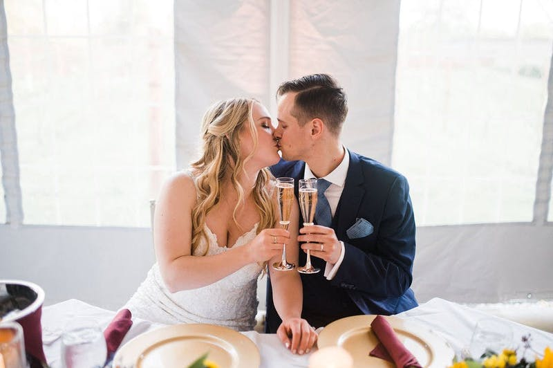 Bride and groom in a deep blue suit, cheersing at the sweetheart table.