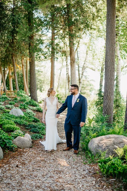 Bride and groom in Navy Suit surrounded by elegant greenery on their wedding day