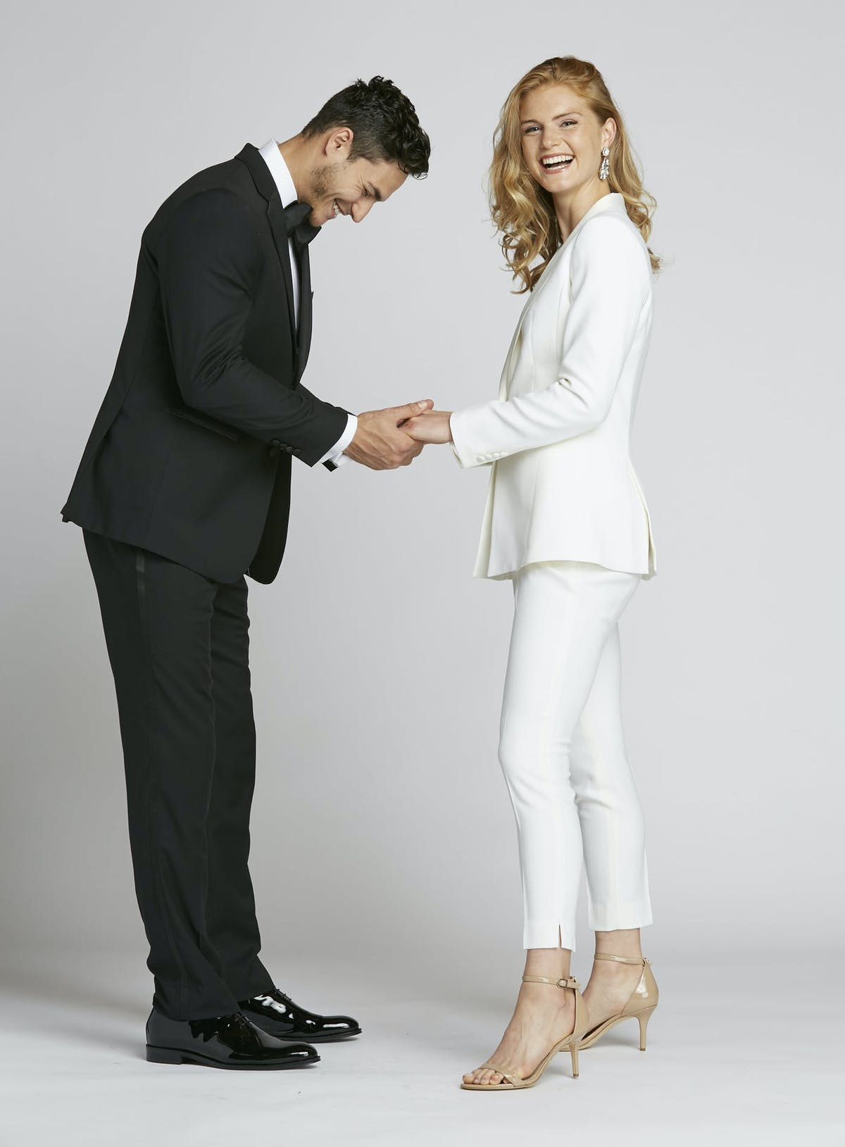 Guide on what to wear to a rehearsal dinner. Instead of a white rehearsal dinner dress, try a white women's tuxedo.